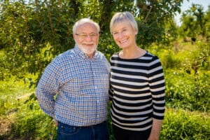 Doug and Cathy Hemly standing in front of their pear orchard
