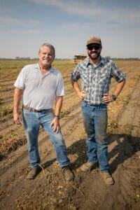 Steve Meek (left) and his son Sam Meek (right) standing in one of their tomato fields being harvested